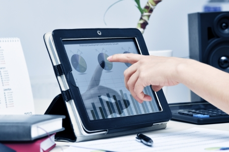 Female hand touching on modern digital tablet pc at the workplace. photo
