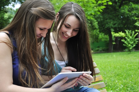 two young girls using a tablet computer outdoor in park Stock Photo - 14119040