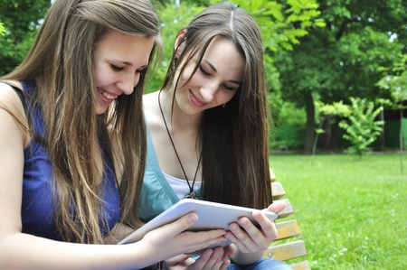 two young girls using a tablet computer outdoor in park Stock Photo - 14118959