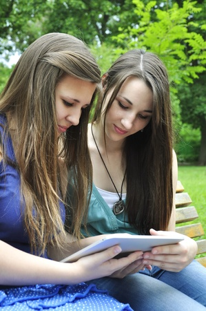 two young girls using a tablet computer outdoor in summer park Stock Photo - 14118962