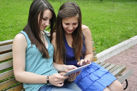 two young girls on bench using a tablet computer outdoor in park Stock Photo - 14118961