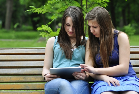 two young girls on bench using a tablet computer outdoor in park Stock Photo - 14119042