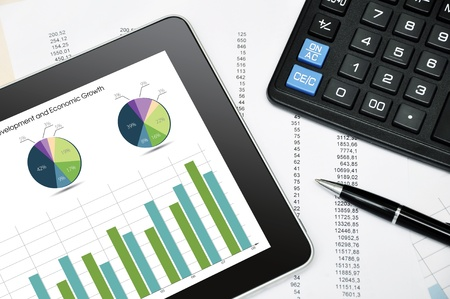 Modern business workplace with digital tablet, calculator, pen and printed data sheet photo