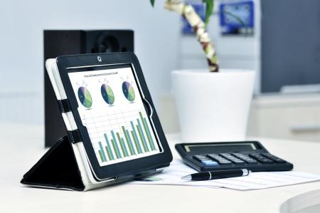 스프레드 시트: 디지털 태블릿, 계산기, 펜 및 인쇄 데이터 시트와 현대 비즈니스 직장 스톡 사진