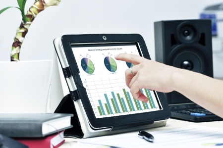Female hand touching on modern digital tablet pc at the workplace. Stock Photo - 14250381