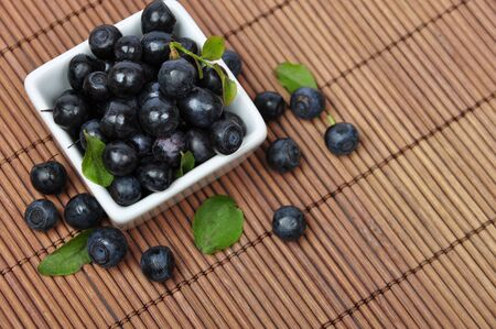 Blueberries in smoll white bowl closeup with leaves photo