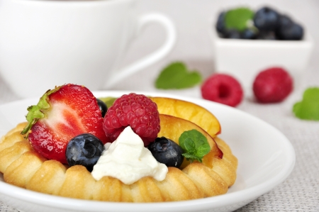 Cottage cheese cream tarts with a slices of berries and fruits photo