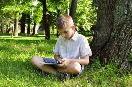 boy using tablet pc outdoor in summer park photo