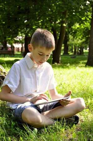 boy using tablet pc on grass in summer park Stock Photo - 14548758