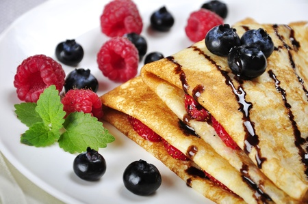 pancakes: Pancakes sereved with raspberries, blueberries and chokolate on plate. Shallow dof Stock Photo