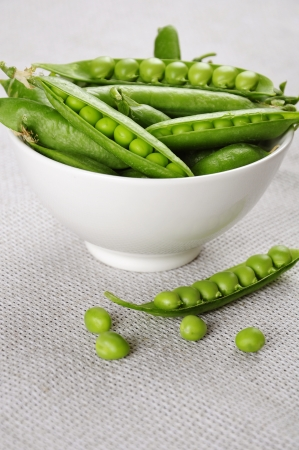 fresh green peas on a white bowl close up photo