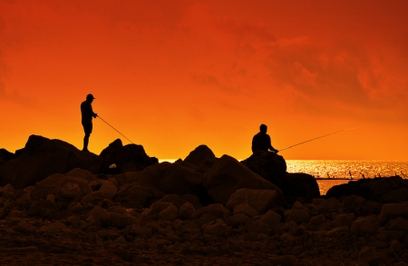 outdoor pursuit: A fishermans in sunset at the coast. Stock Photo