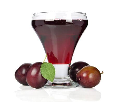 Prugne fresche e un bicchiere pieno di succo di prugne su uno sfondo bianco