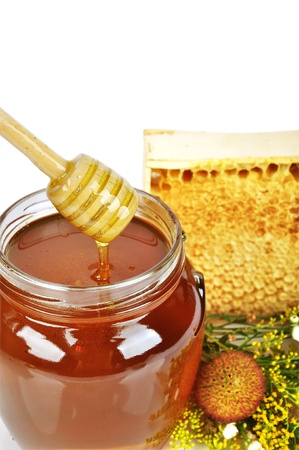 Pot of honey and wooden stick close up photo