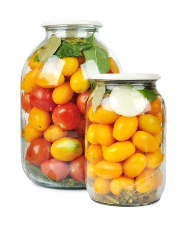 tinned: Preserved red and yellow tomatoes in a glass jar isolated on white background
