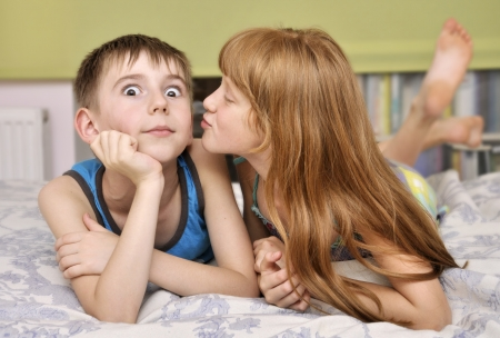 first love: young girl kissing boy on cheek.  Stock Photo