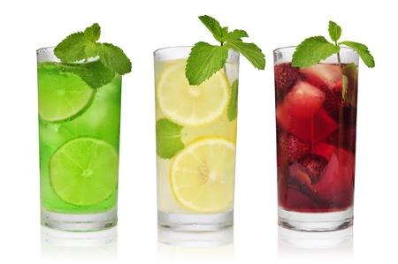 limonada: Tres bebidas refrescantes en glasess con la menta y el hielo aislado