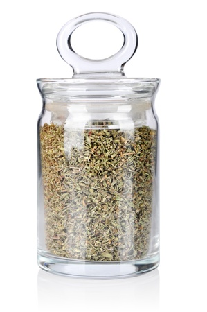 Dried savory in glass bottle isolated on white background photo