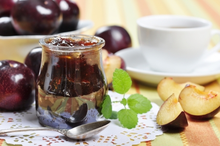 Plum jam in a glass jar and fresh fruits  photo
