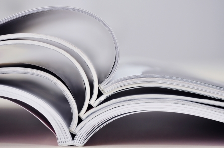 Closeup background of a pile of old magazines with bending pages  Small shallow dof