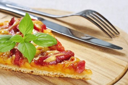 Slice of pizza with knife and fork on wooden cutting board photo