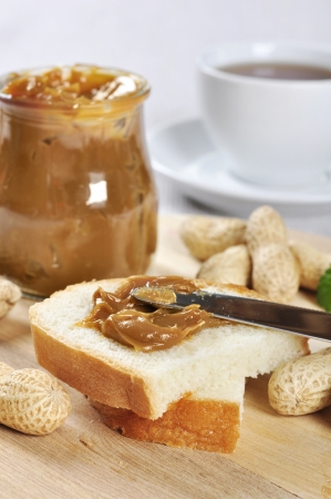 sandwich spread: Fresh homemade peanut butter sandwhich and peanuts on wooden cutting board