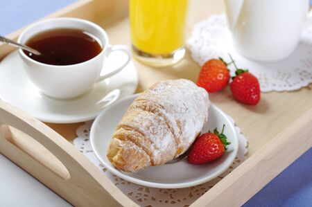 Breakfast with tea and croissants in a wooden tray on table
