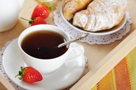 pasteleria francesa: Desayuno con té y croissants en una bandeja de madera sobre la mesa