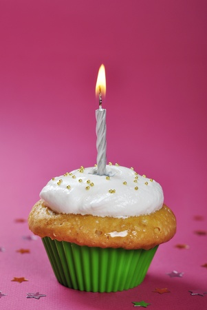 Birthday cupcake with whipped cream and candle on pink background photo