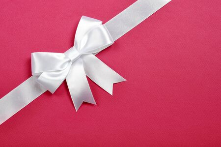 White ribbon whith bow on a pink background photo