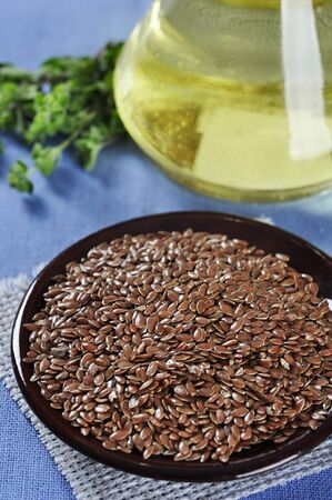 flaxseed: Linseed oil and flax seeds on ceramic plate closeup. Small shallow DOF  Stock Photo