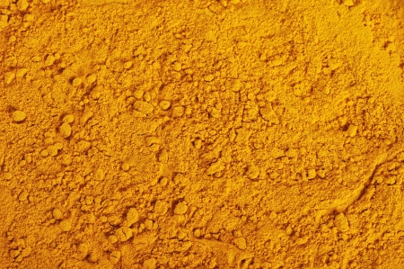 trituration: turmeric powder background, yellow grain abstract texture