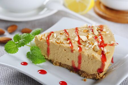 Slice of homemade caramel cheesecake with almond on white plate photo