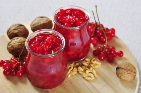 guelder rose berry: Jars with homemade viburnum jam on wooden cutting board Stock Photo