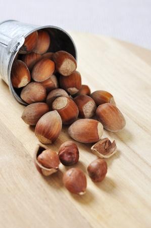 unbroken: hazelnuts in a bucket close-up on a wooden cutting board