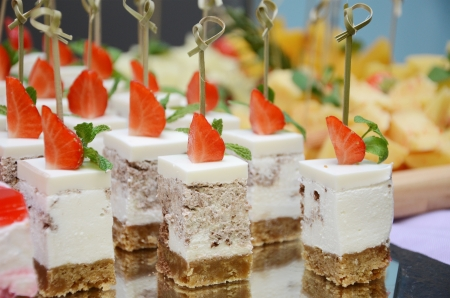 food buffet: Strawberry cakes on tray closeup. Small shallow DOF.