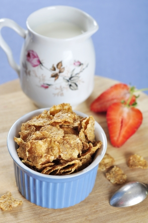 Delicious and nutritious bran flakes cereal in blue bowl with strawberry on wooden cutting board Stock Photo - 16602557