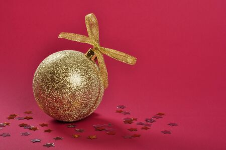 Christmas gold glitter bauble with ribbon and bow over red background. photo