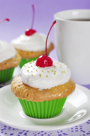 Cupcakes with whipped cream and cherry on violet background Stock Photo - 16724925