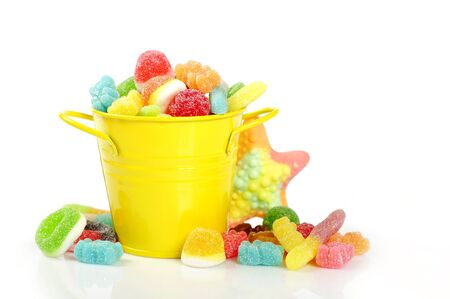 Colorful candies in yellow bucket isolated on white background Stock Photo - 16725105