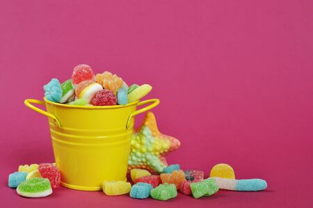 Colorful candies in yellow bucket on pink background photo