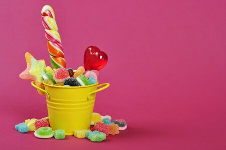 Colorful candies in yellow bucket on pink background Stock Photo - 16725110