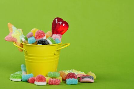 sweet treats: Colorful candies in yellow bucket on green background