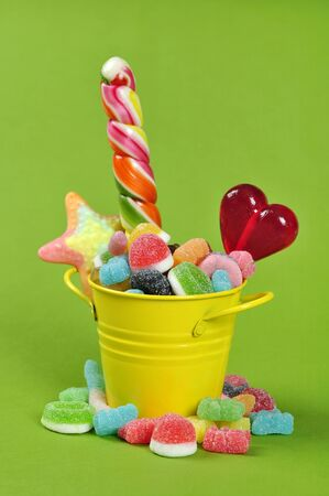 Colorful candies in yellow bucket on green background photo