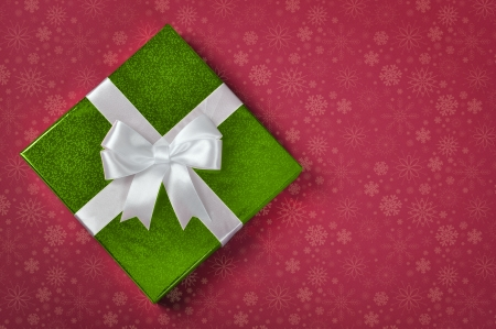 Green gift box with white ribbon on red background photo