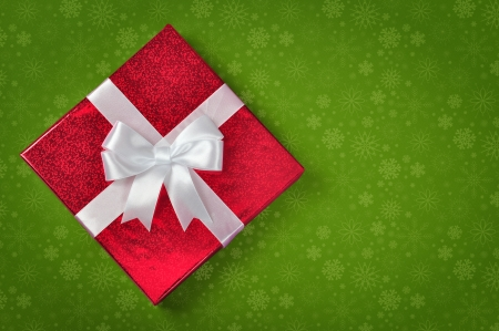 Red gift box with white ribbon on green background photo