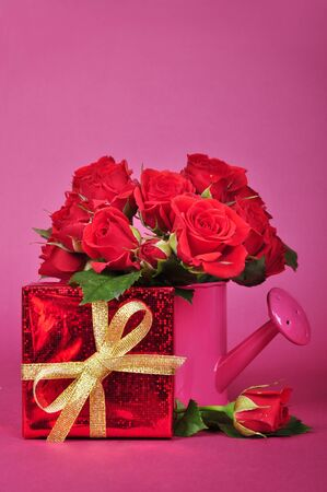bouquet of red roses in a pink watering can with red gift box on a pink background photo