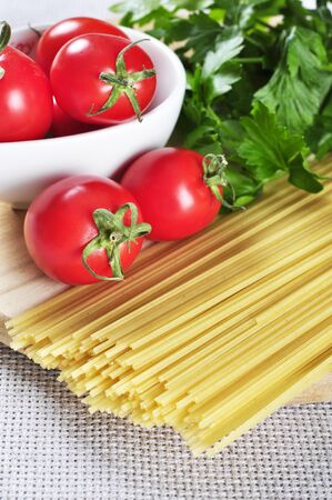 Spaghetti and tomatoes with herbs on an wooden cutting board closeup photo