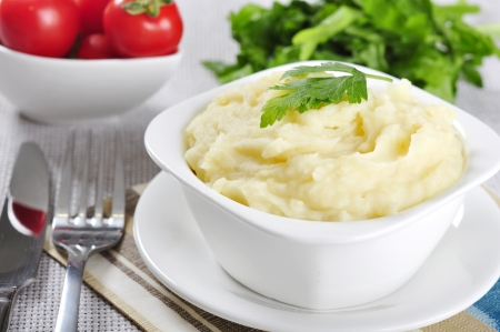 mashed: Mashed potato in white plate with greenery and tomatoes