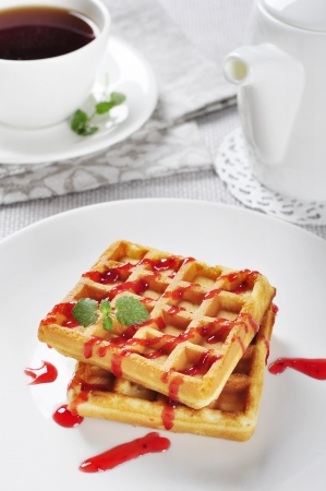 Waffles served with strawberry jam and mint photo
